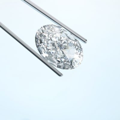 closeup diamond in tweezers on a blue background for Guy Wakeling Jewellery